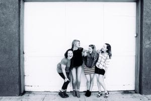 black and white image of four women laughing in front of garage door