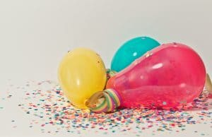 yellow, green, pink balloons lying on confetti