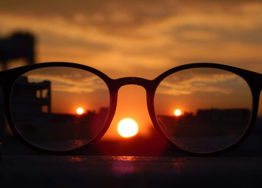 black frame glasses held up to a sunset