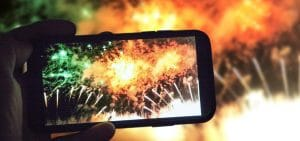 person filming fireworks on their phone
